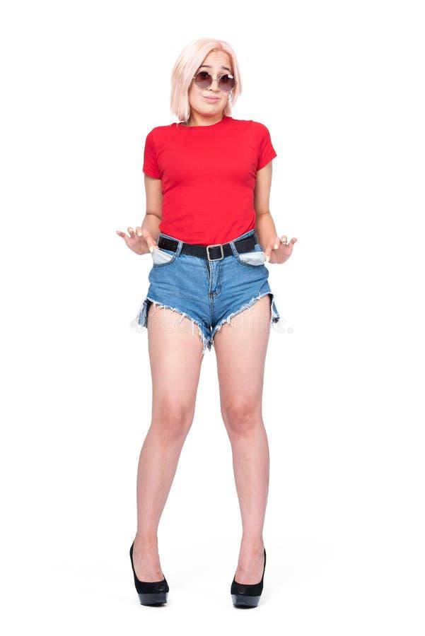 Блондинка маленькой девочки в шортах красной футболки и джинсовой ткани с пятками поворачивает вне его карманы показывая что ника стоковая фотография