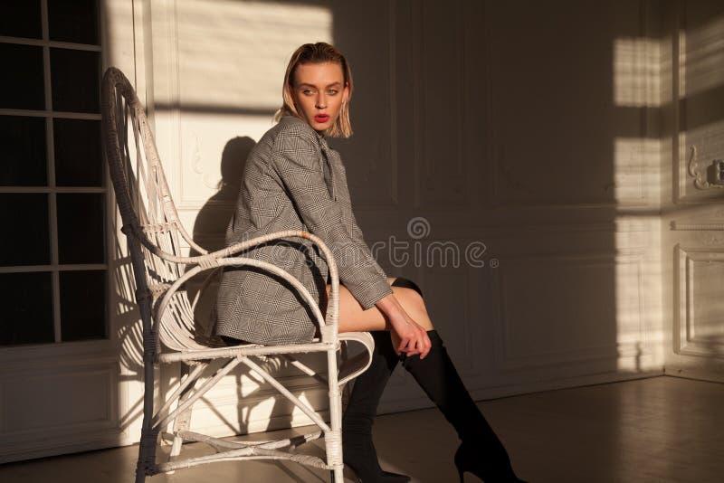 Блондинка модной женщины в женское бельё сидит в белом кресле в комнате стоковое фото rf