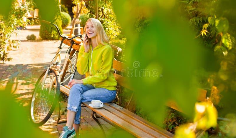 Блондинка насладиться ослабляет в парке или саде Активная девушка с велосипедом Движение и энергия Женщина с велосипедом в зацвет стоковые изображения rf