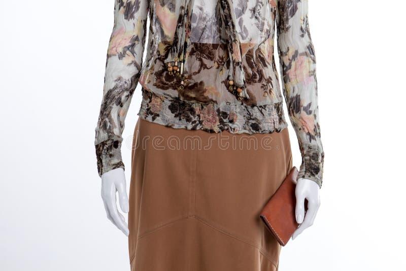 Блузка, юбка коричневого цвета и поднимающее вверх бумажника близкое стоковое фото