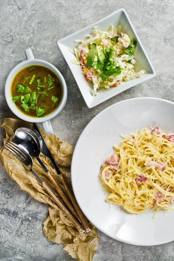 3 блюда в ресторане, макаронных изделиях Carbonara, зеленом салате и курином супе стоковое фото rf