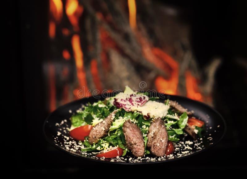 Блюдо говядины или телятины, который служат с листьями салата, томатами и брызгаемые с сыр пармесаном, огнем на предпосылке стоковое изображение