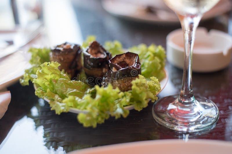 Блюдо кренов закуски овоща заполненного баклажана и бокал вина на таблице в ресторане стоковое изображение