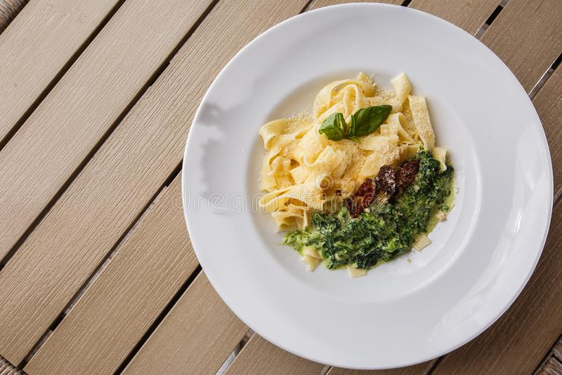 Блюдо макаронных изделий Tagliatelle вегетарианское со шпинатом и высушенными томатами украшенными с базиликом Очень вкусный обед стоковая фотография rf