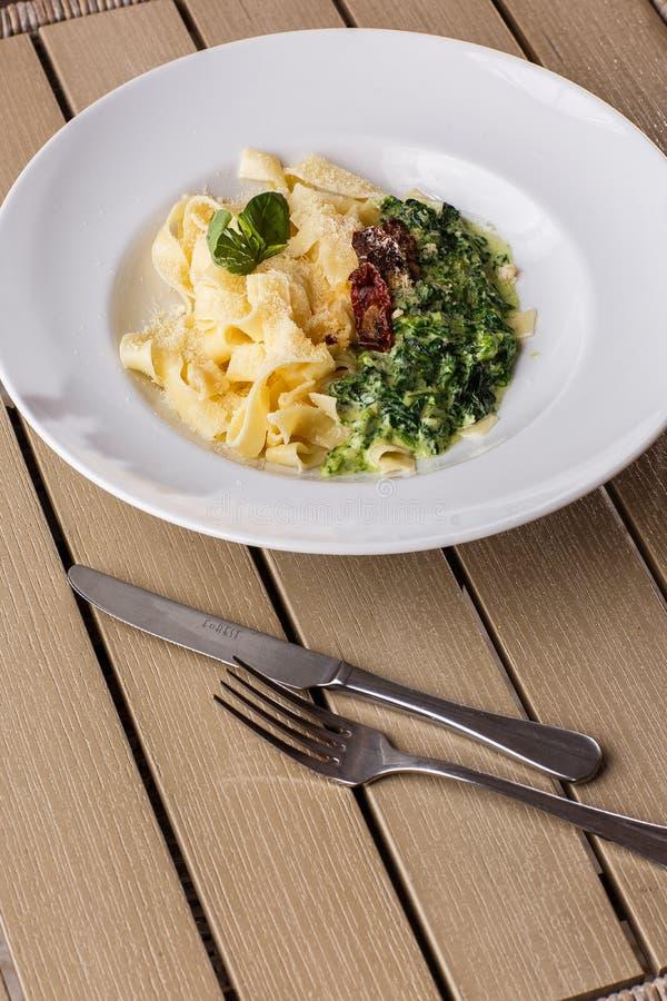 Блюдо макаронных изделий Tagliatelle вегетарианское со шпинатом и высушенными томатами украшенными с базиликом Очень вкусный обед стоковые изображения