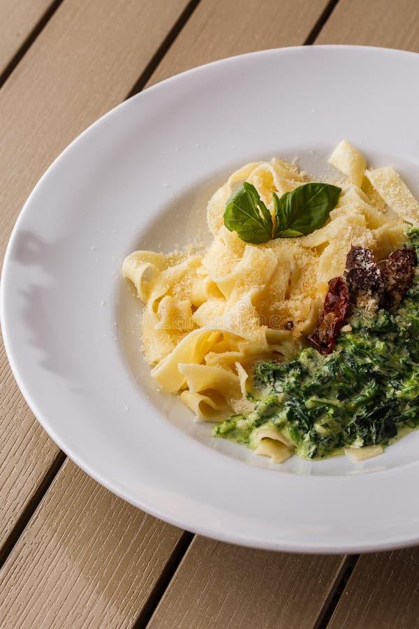 Блюдо макаронных изделий Tagliatelle вегетарианское со шпинатом и высушенными томатами украшенными с базиликом Очень вкусный обед стоковое изображение rf