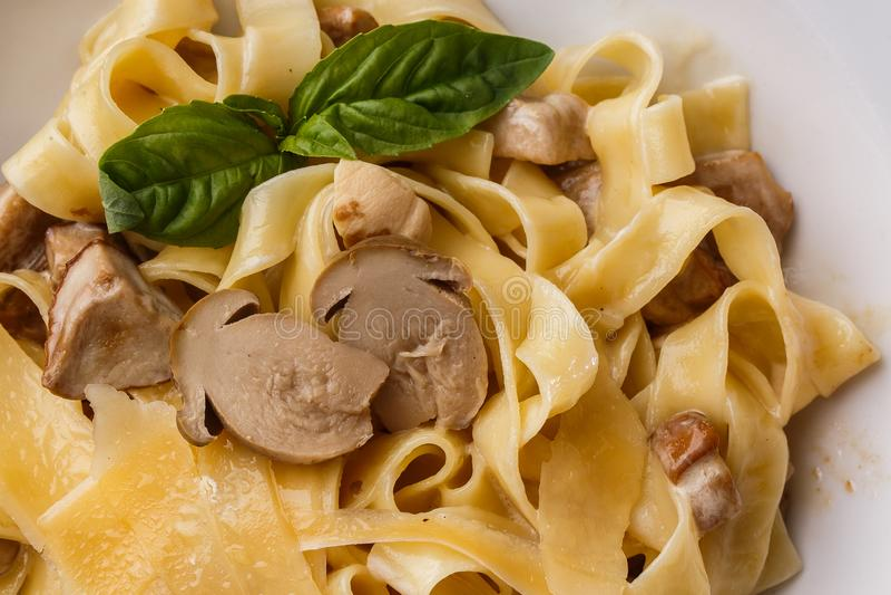 Блюдо макаронных изделий Tagliatelle вегетарианское с грибами украшенными с базиликом Очень вкусный обед с макаронными изделиями  стоковое фото rf