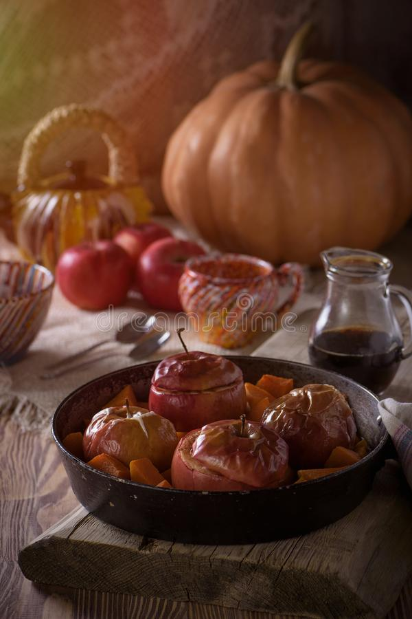 Блюдо осени сладостное испекло яблока и тыкву в сковороде с медом на деревенской предпосылке стоковые фото