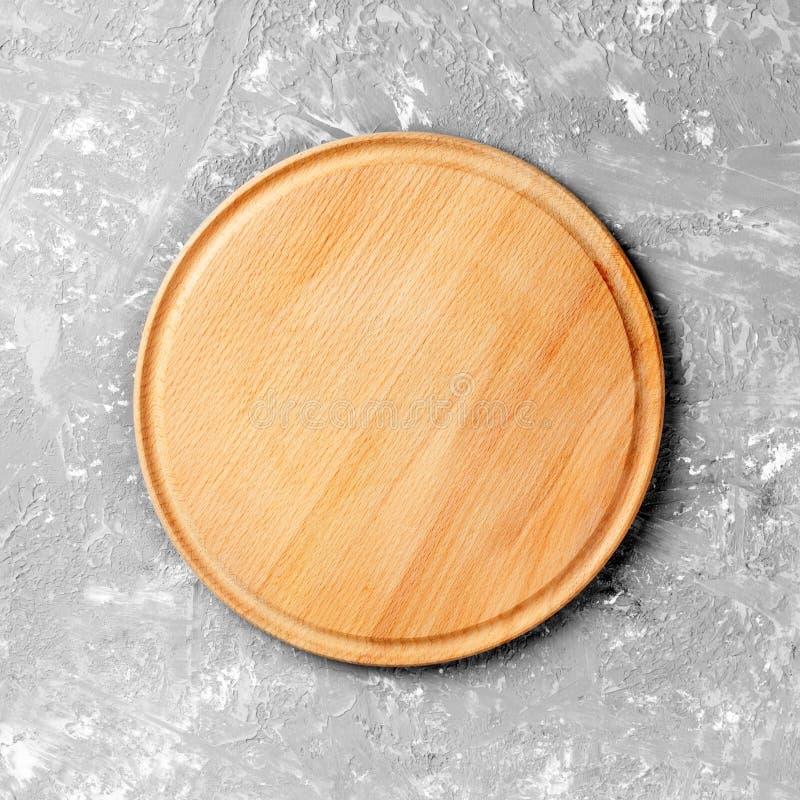 Блюдо пустого круга деревянное на таблице над серой предпосылкой стены цемента, для монтажа дисплея продукта стоковое фото rf