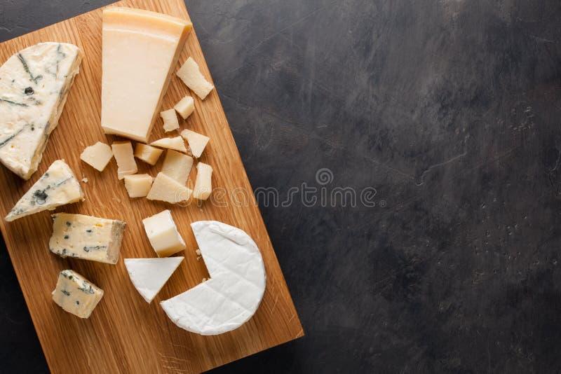 Блюдо сыра дегустации на деревянной плите Еда для вина и романтичное, деликатес сыра на темной каменной таблице Взгляд сверху стоковое фото rf