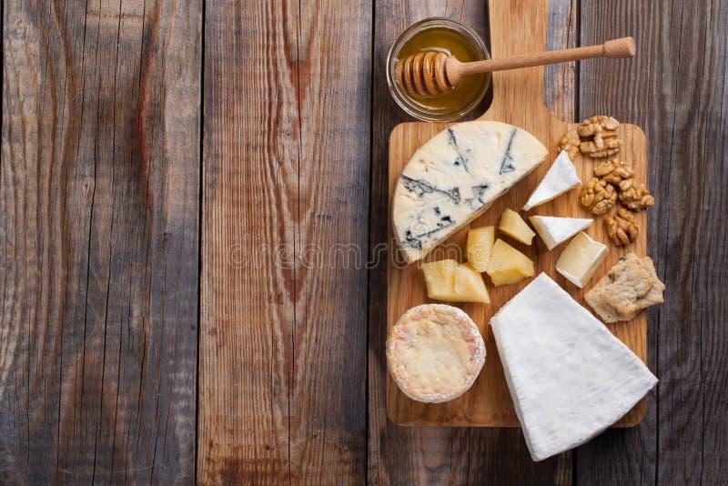 Блюдо сыра дегустации на деревянной плите Еда для вина и романтичное, деликатес сыра на деревянной деревенской таблице Взгляд све стоковая фотография