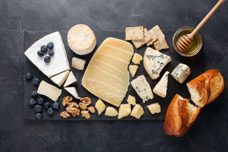Блюдо сыра дегустации на темной каменной плите Еда для вина и романтичная дата, деликатес сыра на черной конкретной предпосылке К стоковые фотографии rf