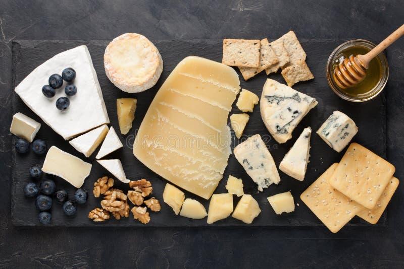 Блюдо сыра дегустации на темной каменной плите Еда для вина и романтичная дата, деликатес сыра на черной конкретной предпосылке К стоковые изображения rf