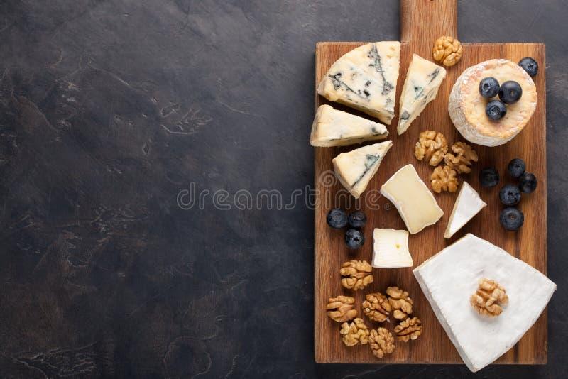 Блюдо сыра дегустации на темной каменной плите Еда для вина и романтичная дата, деликатес сыра на черной конкретной предпосылке К стоковая фотография