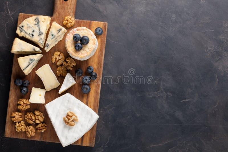 Блюдо сыра дегустации на темной каменной плите Еда для вина и романтичная дата, деликатес сыра на черной конкретной предпосылке К стоковое фото rf