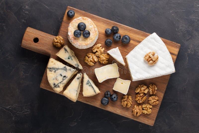 Блюдо сыра дегустации на темной каменной плите Еда для вина и романтичная дата, деликатес сыра на черной конкретной предпосылке К стоковая фотография rf
