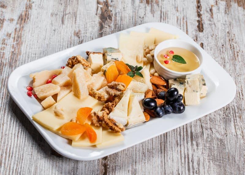 Блюдо сыров гарнированное с грушей, медом, грецкими орехами в плите над деревенской предпосылкой Установленные закуски закусок и  стоковые изображения rf