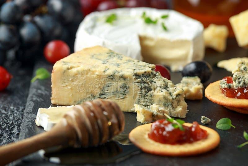 Блюдо сыров, который служат с виноградинами, чатни эля, мед, шутихи на каменной доске Бри, чеддер, красный Лестер стоковое изображение rf