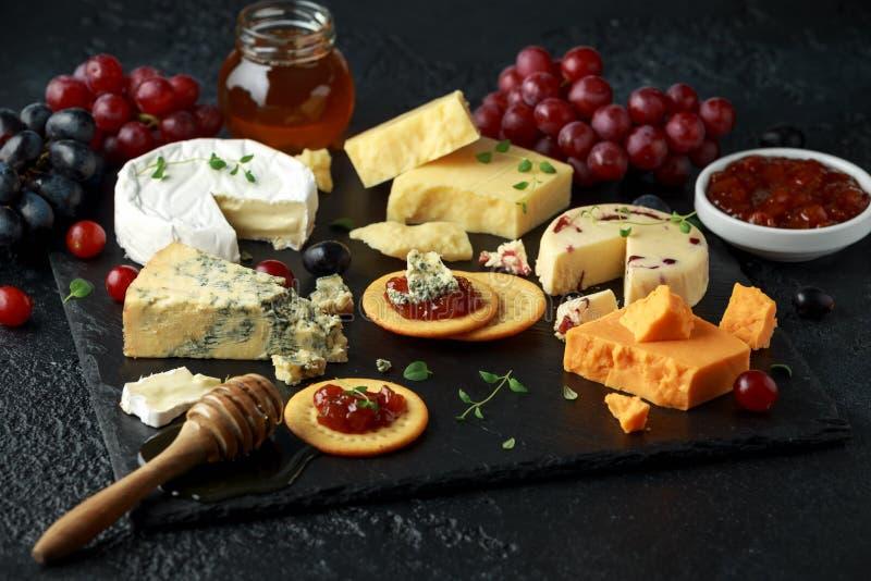 Блюдо сыров, который служат с виноградинами, чатни эля, мед, шутихи на каменной доске Бри, чеддер, красный Лестер стоковое фото