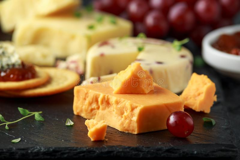 Блюдо сыров, который служат с виноградинами, чатни эля, мед, шутихи на каменной доске Бри, чеддер, красный Лестер стоковые фотографии rf