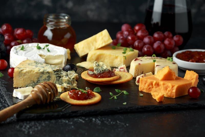 Блюдо сыров, который служат с виноградинами, чатни эля, мед, шутихи на каменной доске Бри, чеддер, красный Лестер стоковое изображение
