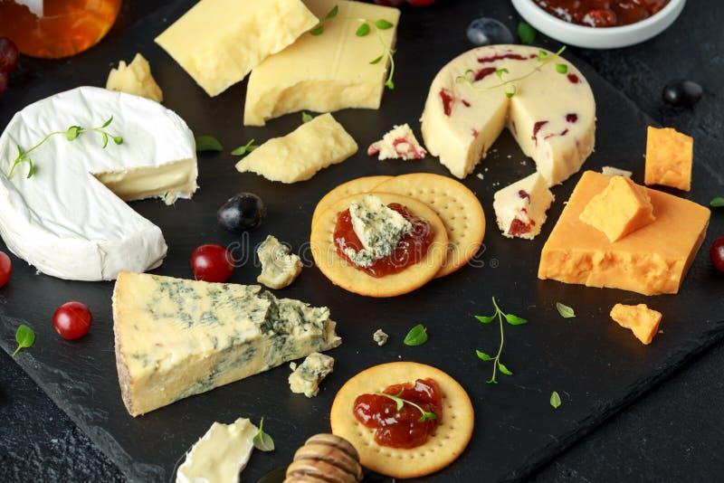 Блюдо сыров, который служат с виноградинами, чатни эля, мед, шутихи на каменной доске Бри, чеддер, красный Лестер стоковая фотография rf