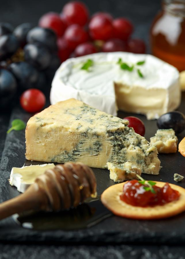 Блюдо сыров, который служат с виноградинами, чатни эля, мед, шутихи на каменной доске Бри, чеддер, красный Лестер стоковое фото rf