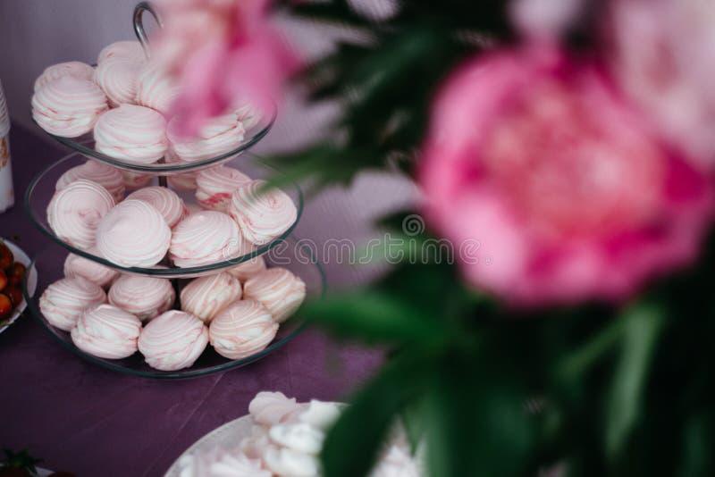блюдо с розовым зефиром, флористическим украшением таблицы стоковые изображения