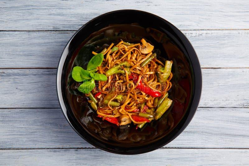 Блюдо традиционного китайския на круглой плите, лапшах риса, капусте капусты зеленой и зажаренных овощах, красных томатах вишни стоковая фотография rf