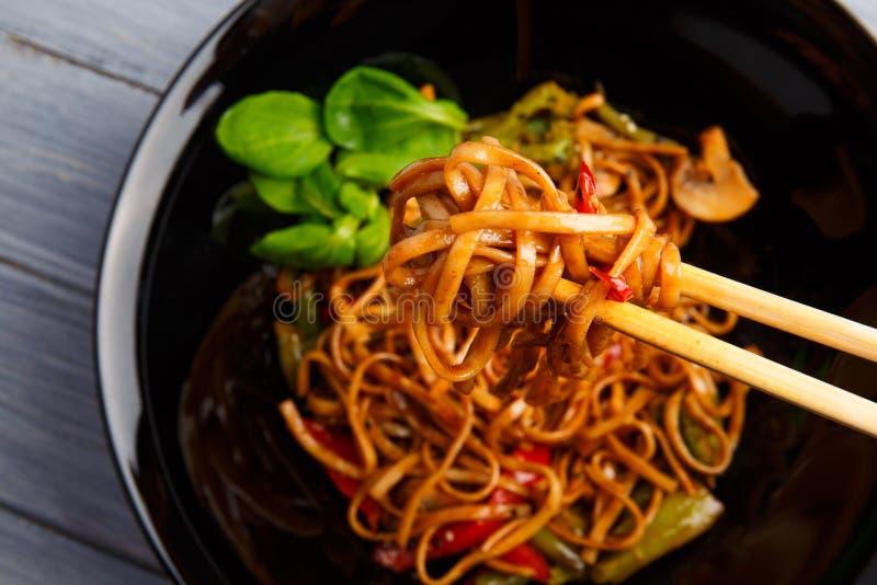Блюдо традиционного китайския на круглой плите, лапшах риса, капусте капусты зеленой и зажаренных овощах стоковая фотография