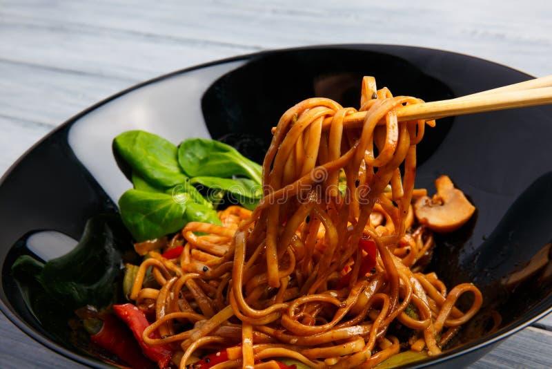 Блюдо традиционного китайския на круглой плите, лапшах риса, капусте капусты зеленой и зажаренных овощах стоковое изображение