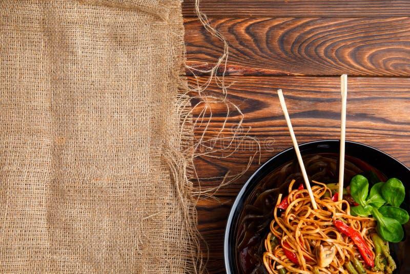Блюдо традиционного китайския на круглой плите, лапшах риса, капусте капусты зеленой и зажаренных овощах стоковое фото