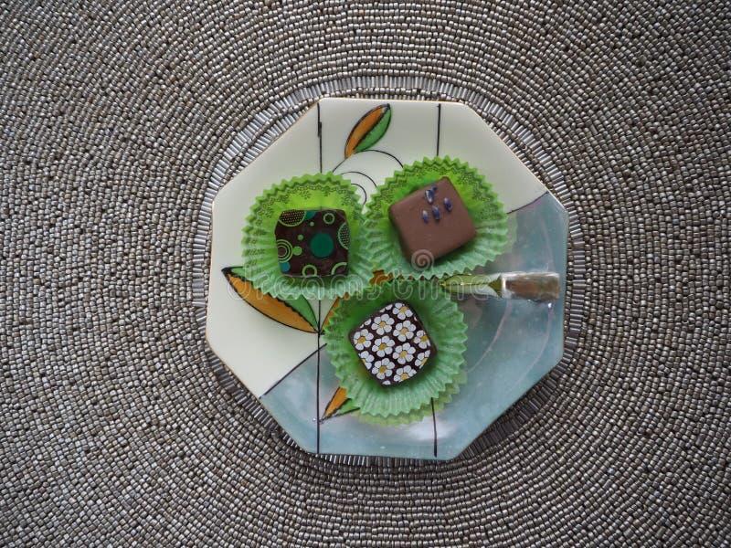Блюдо фарфора с 3 конфетами шоколада на вышитом бисером Placemat стоковое фото
