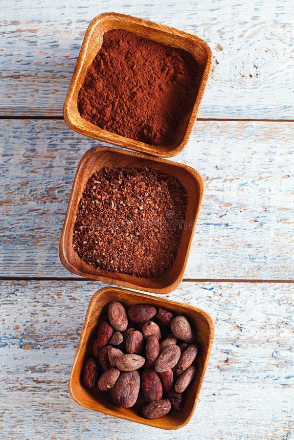 Бобы кака, порошок и заскрежетанный шоколад в деревянных шарах, белых стоковое фото