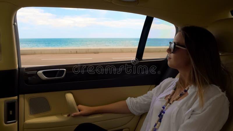 Богатая дама имея отключение в роскошном автомобиле на дороге набережной, роскошные каникулы в курорте стоковое изображение