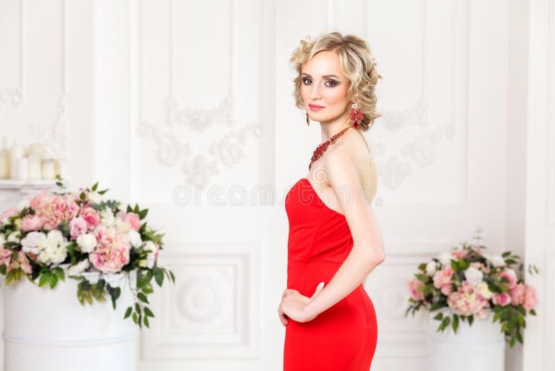 Богато дама представляя в красных платье и ювелирных изделиях смотрящ камеру, стоковое изображение