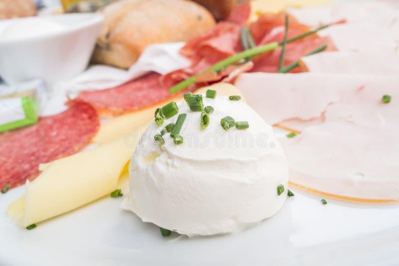 Богато покрытая таблица завтрака с ветчиной и сыром с chives на ем стоковое изображение