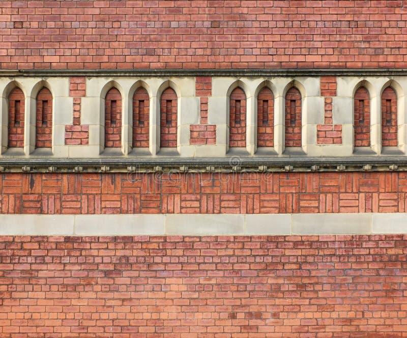 Богато украшенная красная кирпичная стена построенная со сложными картинами и сводом готического стиля каменным декоративным дета стоковое фото rf