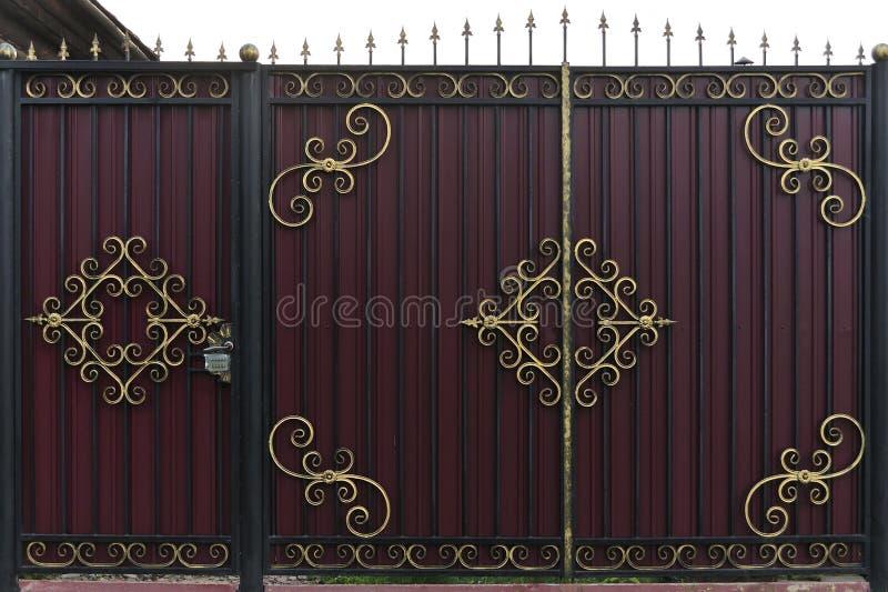 Богато украшенные и красивые чугунные ворота загородки покрасили коричневый цвет и золото шарлаха Фото естественных старых ворот  стоковые изображения