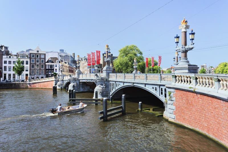 Богато украшенный стародедовский мост с шлюпкой в Амстердам стоковое фото