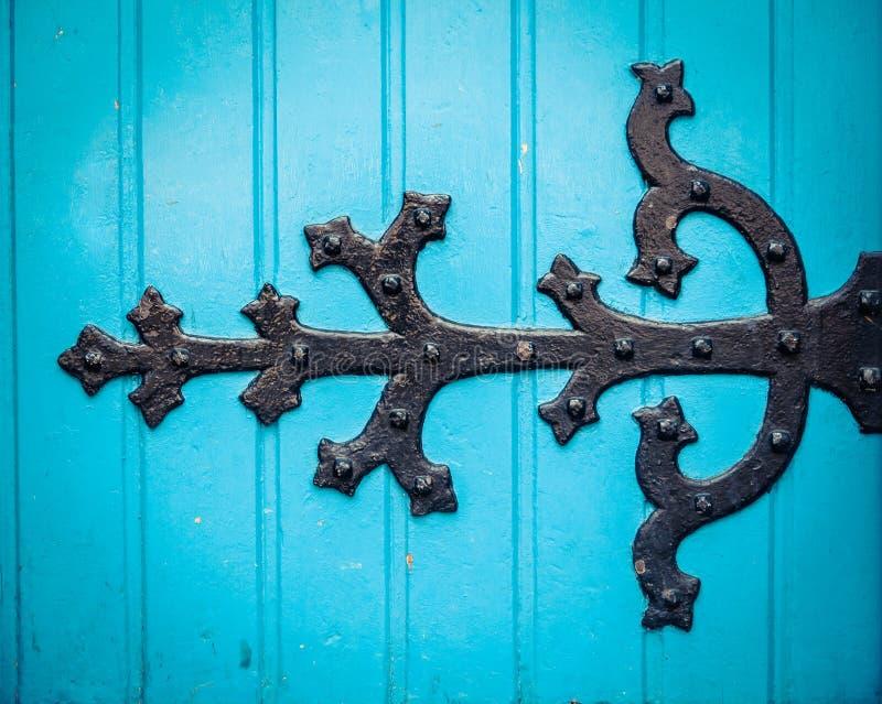 Богато украшенный шарнир на голубой двери церков стоковое изображение