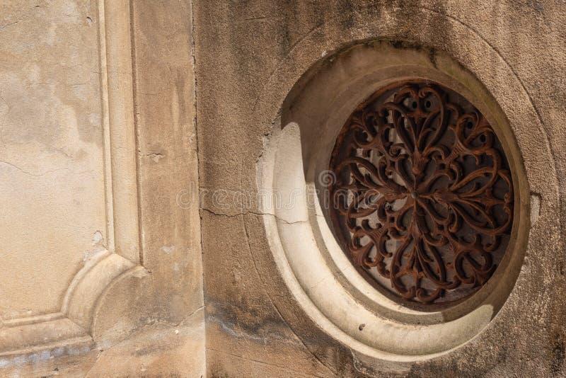 Богато украшенным заржаветый кругом гриль металла установил в сформированную бетонную стену стоковые изображения rf