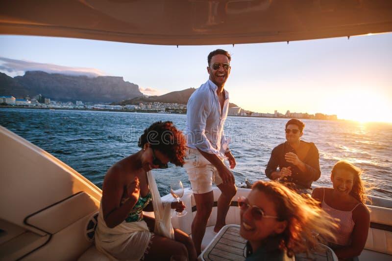 Богатые человеки наслаждаясь партией шлюпки захода солнца стоковая фотография rf