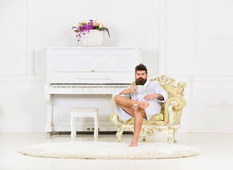 Богатый парень сидя в кресле и выпивая чае или кофе Бородатый парень в белой комнате Совершенная концепция утра стоковые фотографии rf
