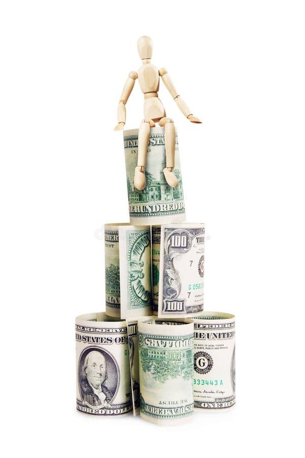 Богатый человек сидит на пирамиде долларовых банкнот стоковые фото