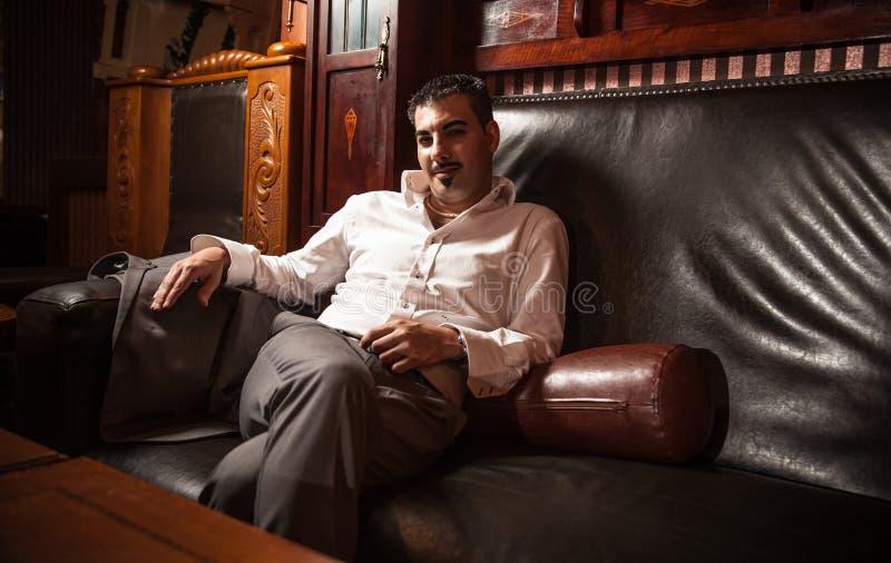Богатый человек сидя на винтажной кожаной софе стоковое изображение rf