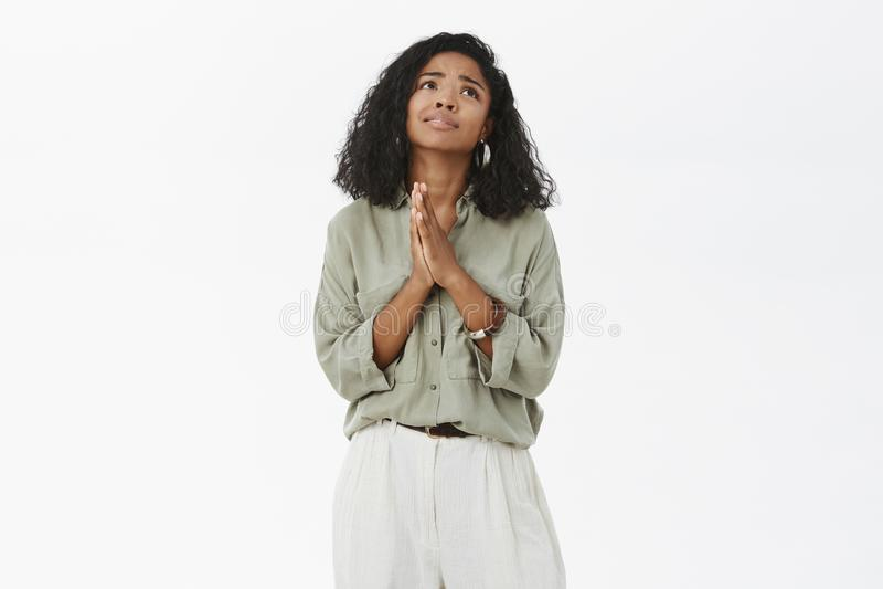 Бог пожалуйста делает мою мечту прийти верно Портрет хмурой надеющийся очаровательной Афро-американской подруги в блузке и брюках стоковые изображения rf