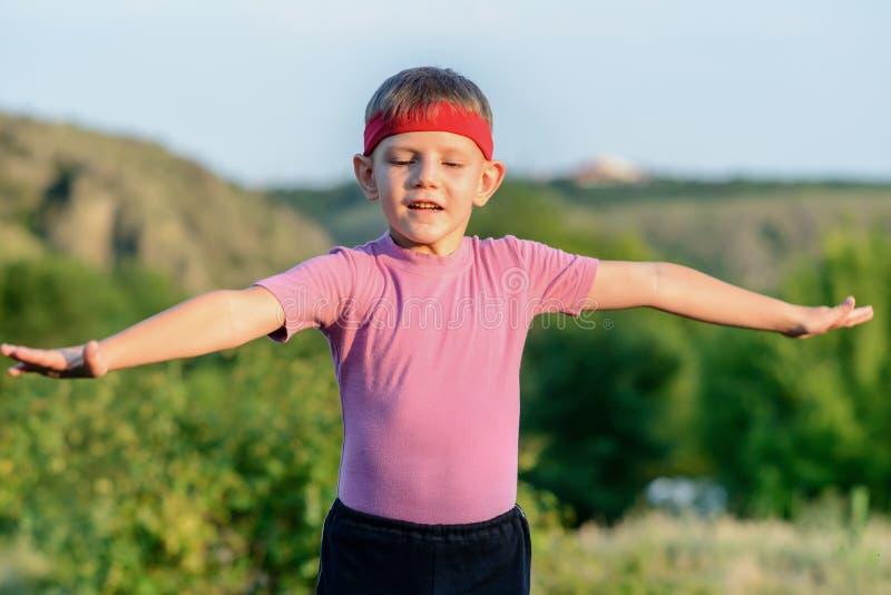 Боевые искусства серьезного мальчика практикуя на поле стоковые изображения rf