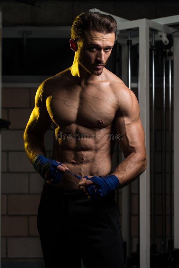 Боец кладя голубые ремни на его руки стоковое фото rf