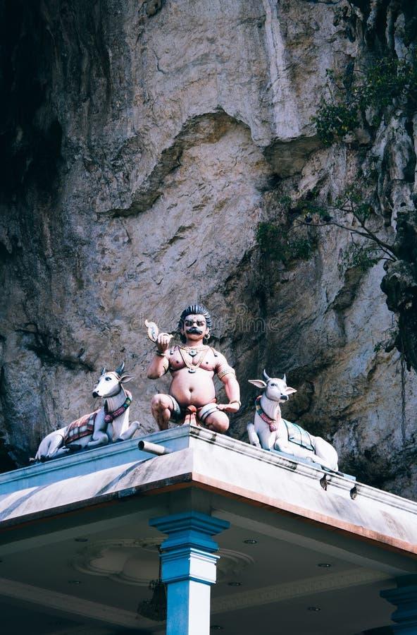 Божества статуи индусские на крыше виска в пределах Batu выдалбливают Batu выдалбливает - комплекс пещер известняка в Куалае-Лумп стоковое фото rf